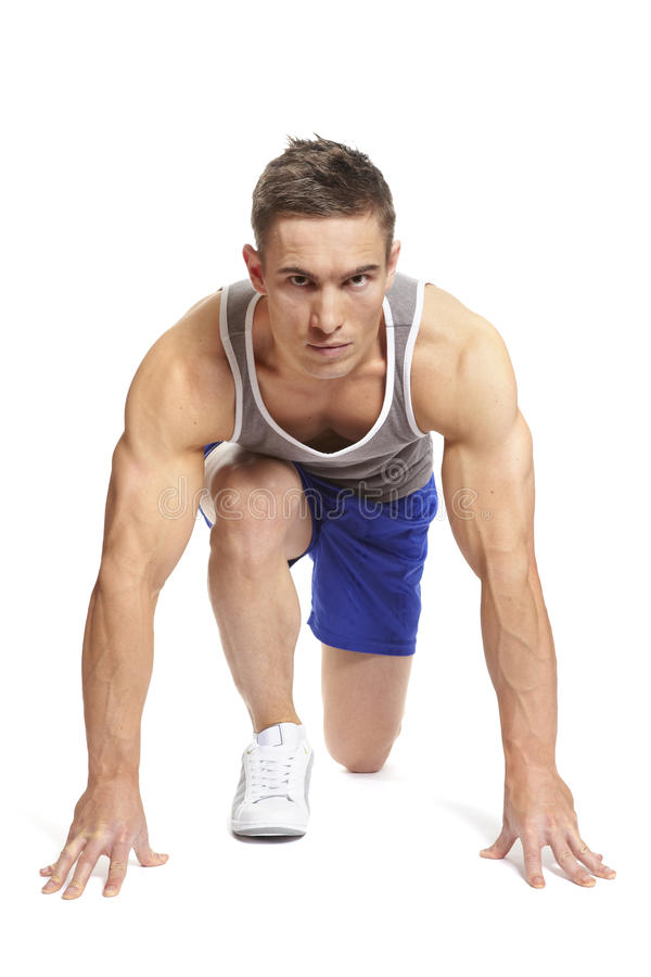 Muscular young man ready to race in sports outfit. Muscular young man in starting position and ready to race in sports outfit on white background royalty free stock photo