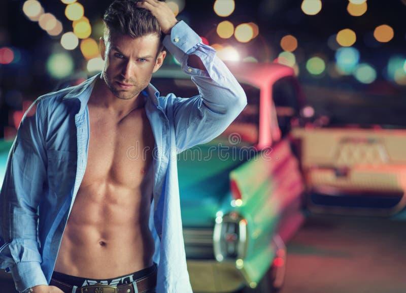 Muscular young man with the retro car stock photos