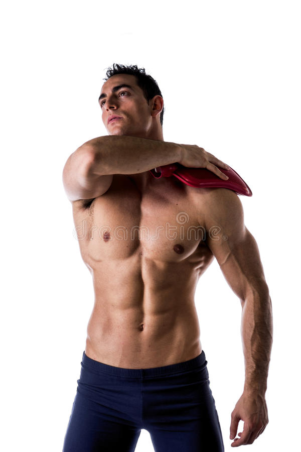 Muscular young man with shoulder pain, holding hot water bottle royalty free stock image