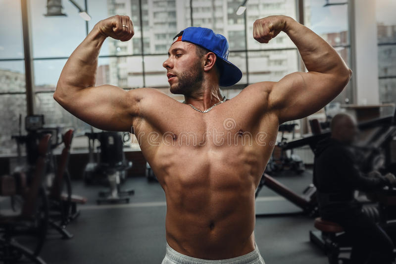 Muscular young man shows his muscles in the gym. royalty free stock images