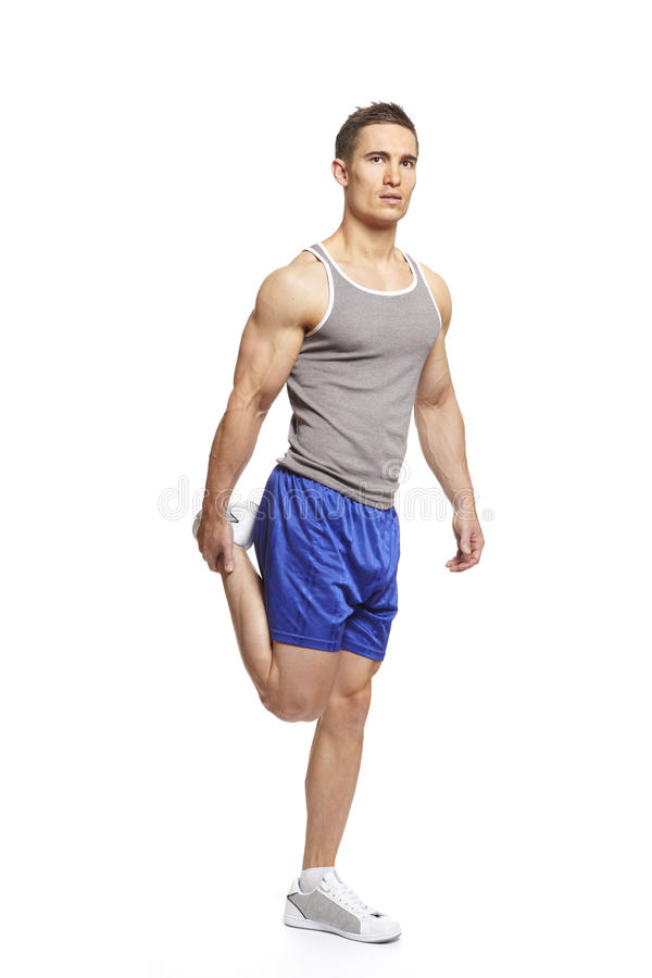Muscular young man stretching in sports outfit royalty free stock photography