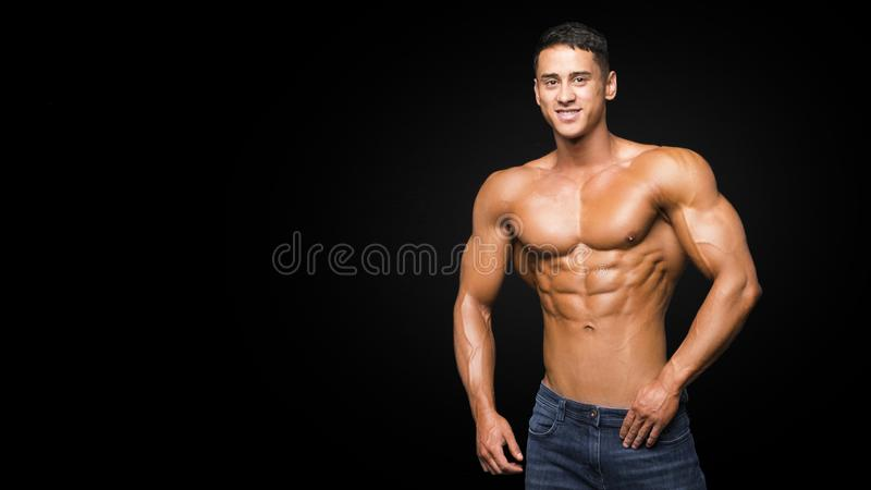 Muscular young man in studio on dark background shows the different movements and body parts stock photo
