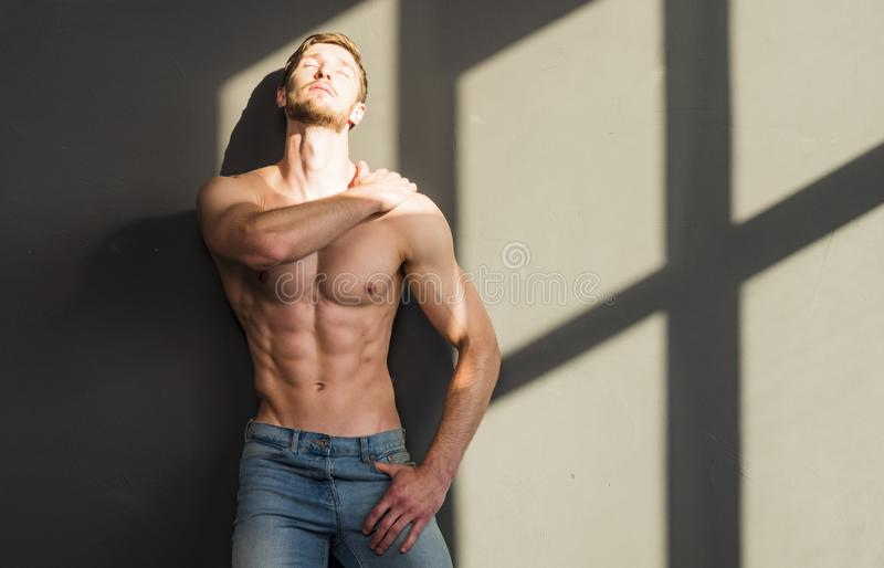 Muscular young man in studio on dark background shows the different movements and body parts stock image
