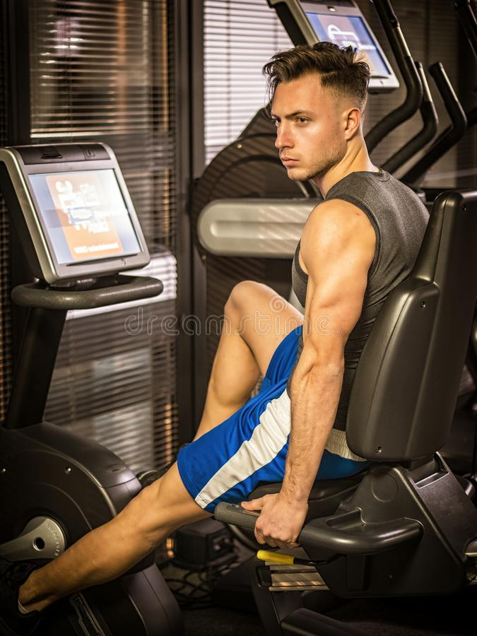 Muscular young man, training legs on gym machine. Or stationary bike royalty free stock image