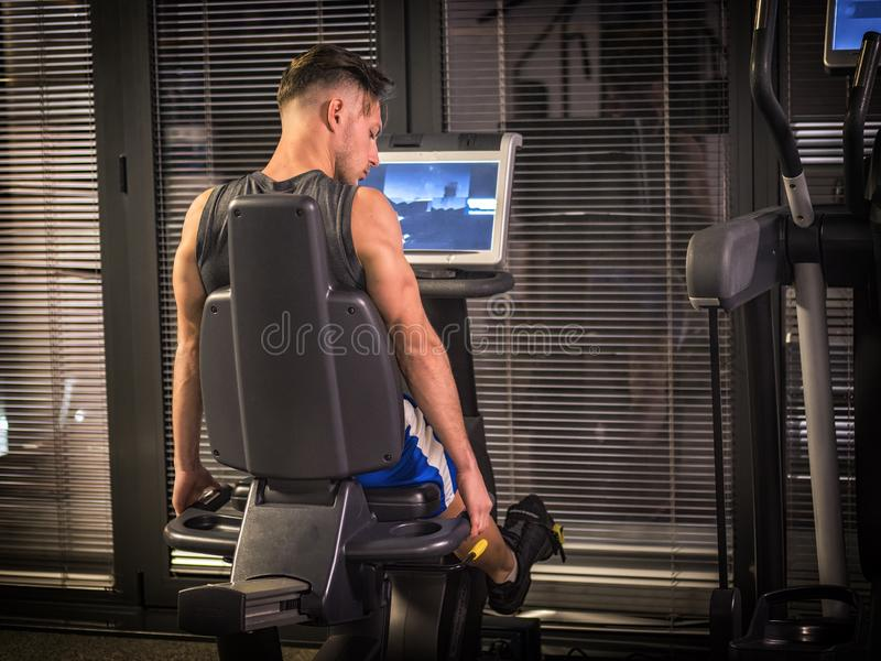Muscular young man, training legs on gym machine. Or stationary bike royalty free stock images