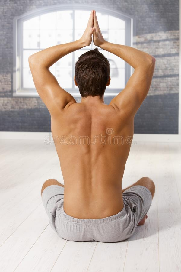 Muscular young man in yoga exercise royalty free stock photography