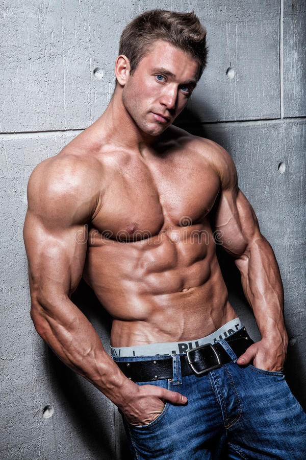 Muscular young guy posing in jeans and bare-chested stock images