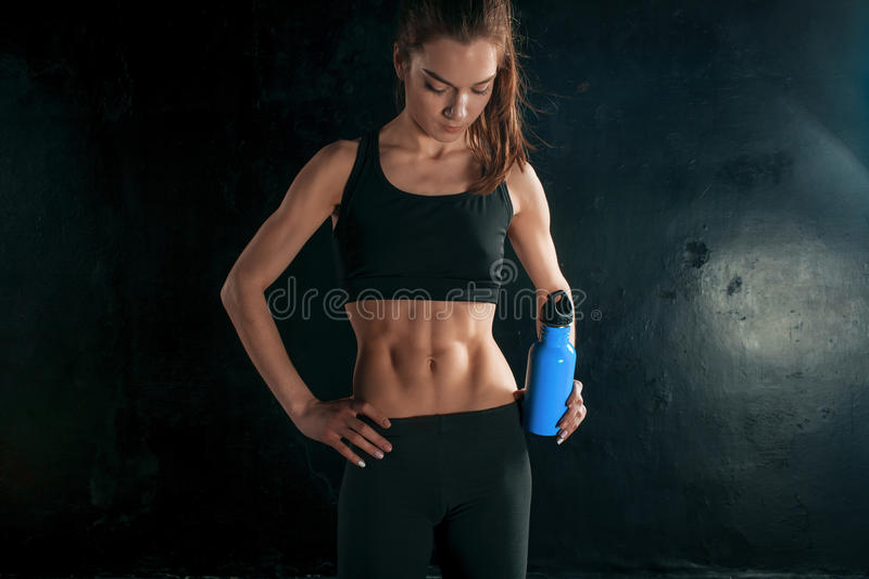 Muscular young woman athlete with a water on black stock photo