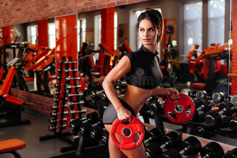 Muscular young woman with beautiful body doing exercises with dumbbell. Sporty girl lifting weights in gym royalty free stock images