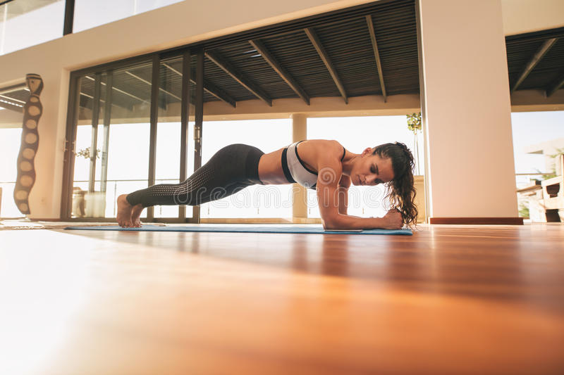 Muscular young woman doing push ups at home royalty free stock photo