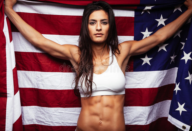Muscular young woman holding american Flag. Portrait of proud female athlete holding American Flag against. Muscular young woman looking confidently at camera stock image