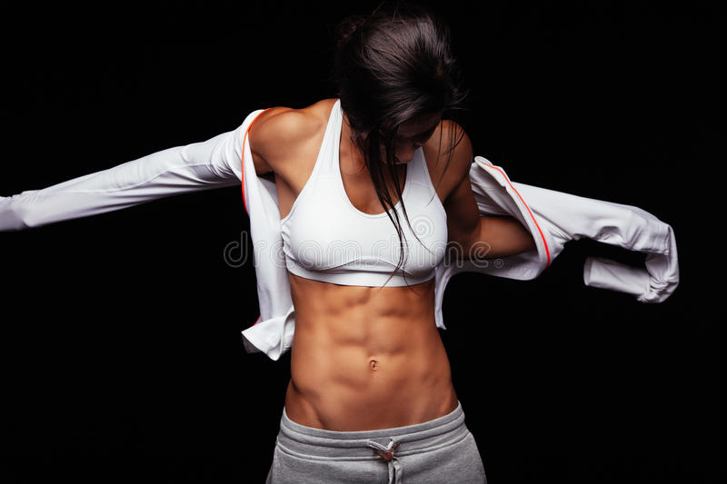 Muscular young woman wearing sports jacket stock images