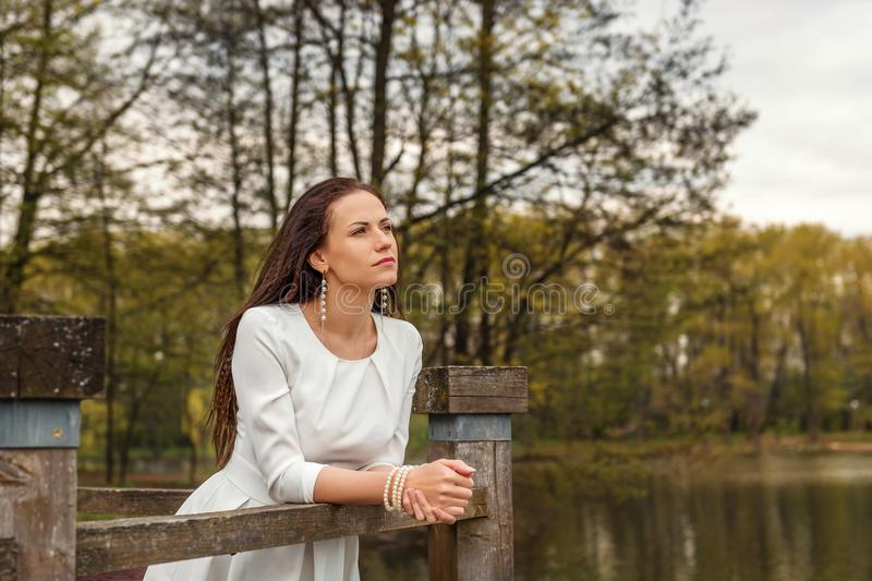 Dreaming pensive young woman stands leaning on a railing of a wooden bridge in a white dress looking forward royalty free stock photography