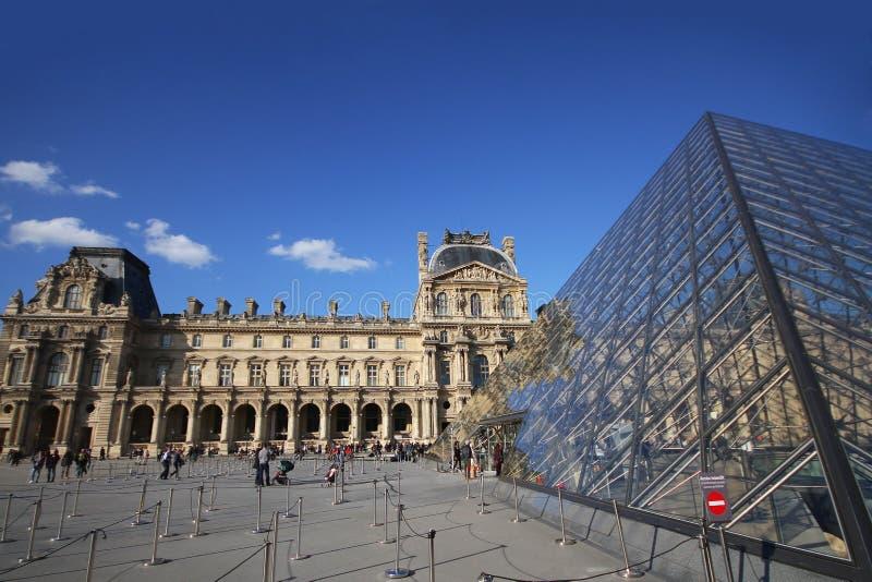 Musee du Louvre, det upplysta attraktiva museet i trevlig solig dag, glassed pyramid i Europa, Paris, Frankrike, turist arkivfoto