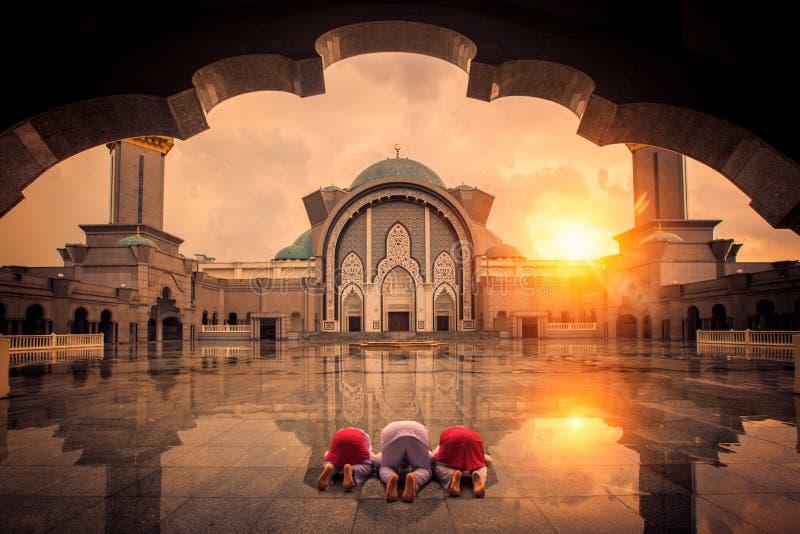 Muselmanen chilgren synd och ber i moské arkivbild