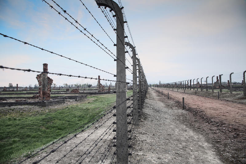 Museum Auschwitz - Birkenau. Holocaust Memorial Museum. Barbed wire and fance around a concentration camp. Ruins of destroyed barracks royalty free stock images