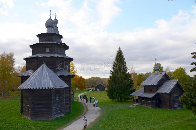 Museum of Folk Wooden Architecture `Vitoslavitsy` in Veliky Novgorod, Russia. People walk between the wooden buildings in autumn stock photos