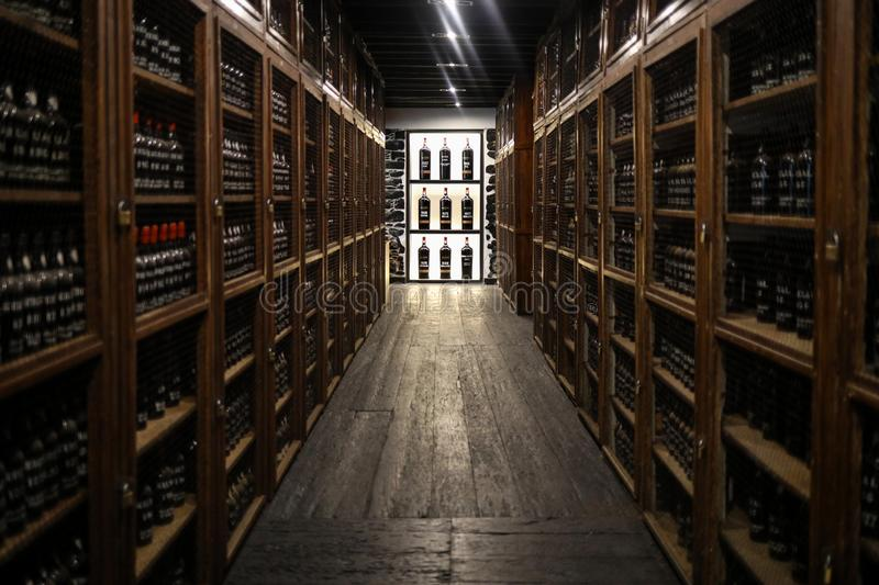 Museum - repository of expensive vintage wine Madera. Long rows of shelves made of bottles of wine. funchal, Madera. Portugal. Funchal, Madeira, Portugal - April royalty free stock images