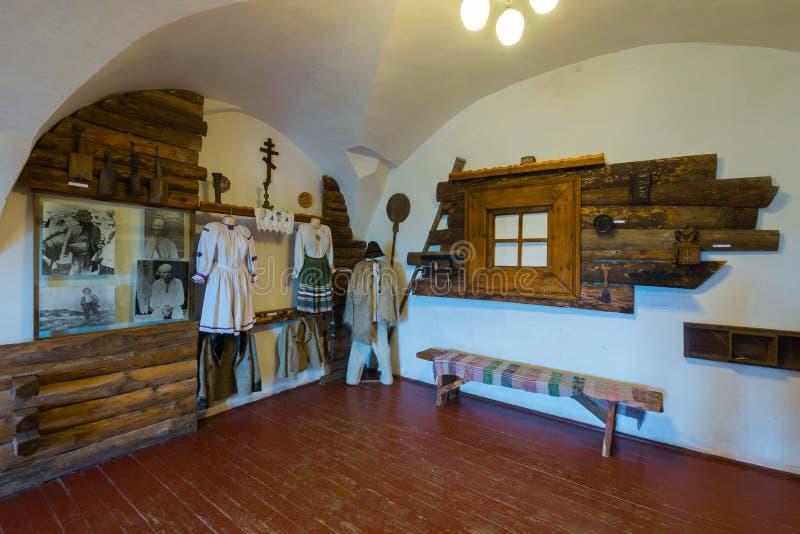 Museumsausstellung, welche die traditionelle ukrainische Hütte mit Einzelteilen der nationalen Kleidung zeigt lizenzfreie stockfotografie