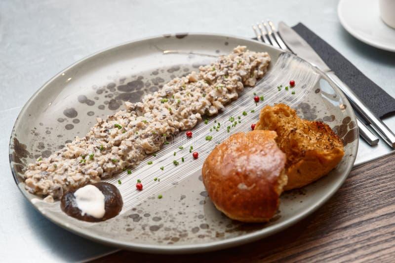 Mushroom caviar on plate, Nordic cuisine. Mushroom caviar and grilled brioche on plate, Nordic cuisine dish stock photography