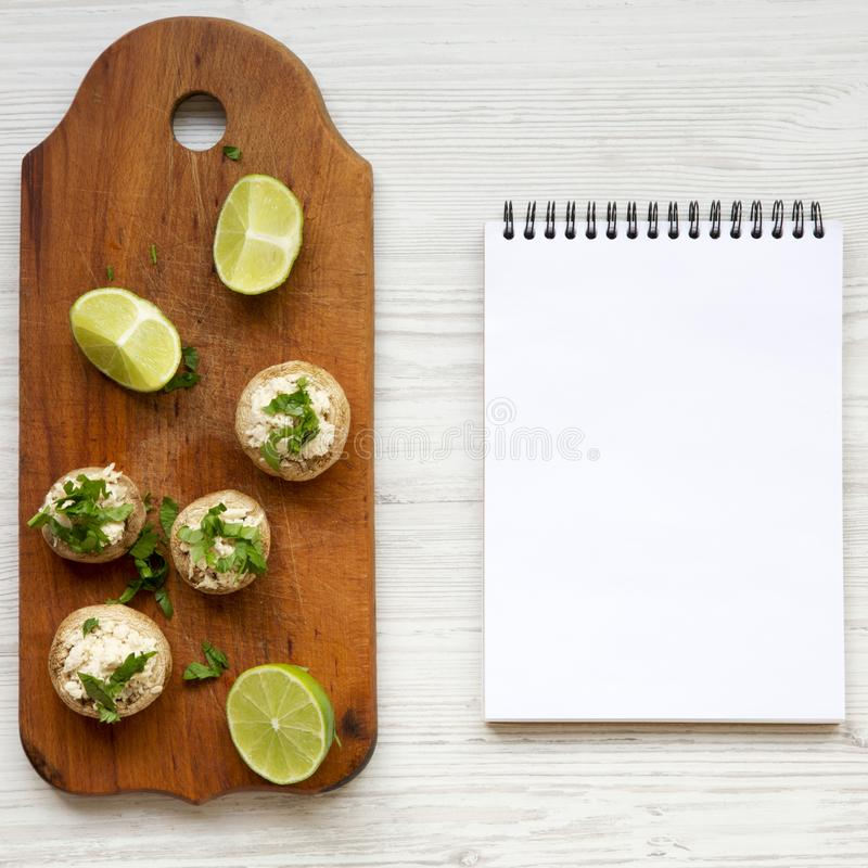 Mushroom and chicken puree, lime and notebook on a white wooden surface, top view. Flat lay, overhead. Copy space.  stock photography