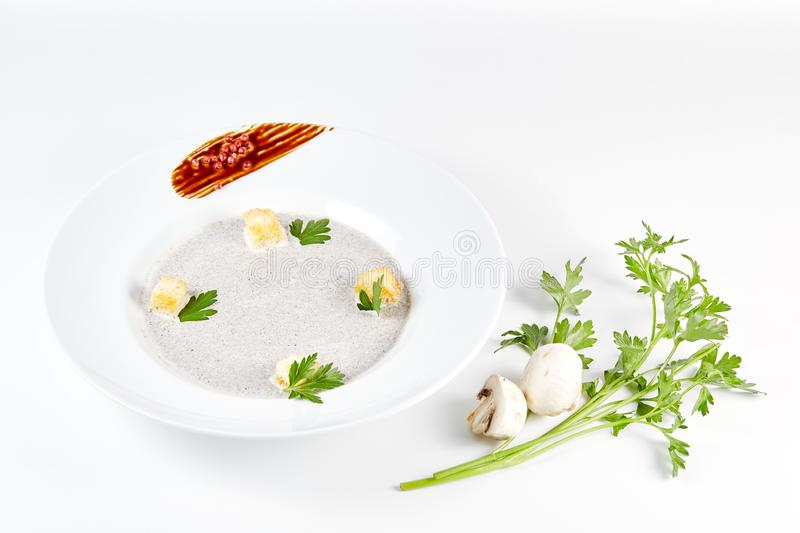 Mushroom cream soup with croutons, herbs and spices over white background close up - homemade vegan vegetarian diet stock photography