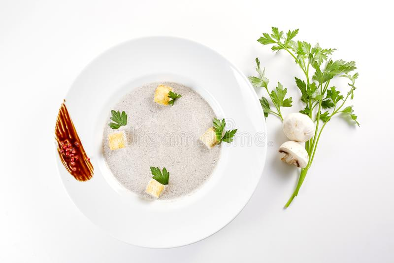 Mushroom cream soup with croutons, herbs and spices over white background close up - homemade vegan vegetarian diet royalty free stock photos