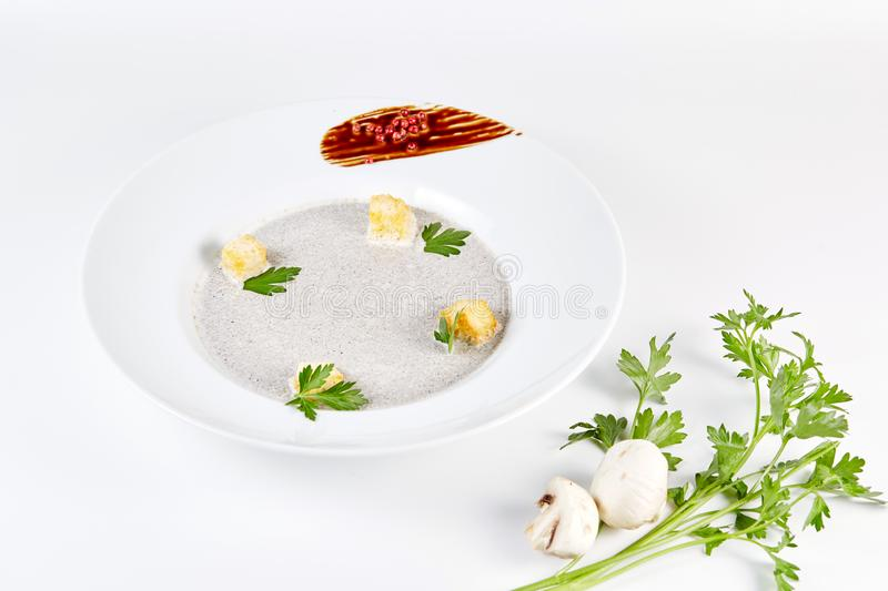 Mushroom cream soup with croutons, herbs and spices over white background close up - homemade vegan vegetarian diet royalty free stock image
