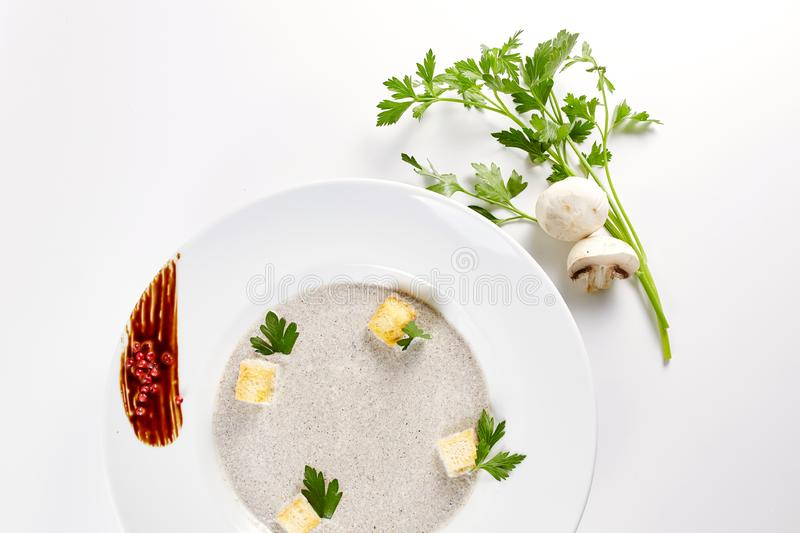 Mushroom cream soup with croutons, herbs and spices over white background close up - homemade vegan vegetarian diet royalty free stock photo