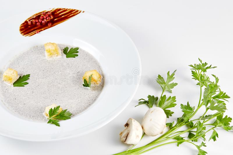 Mushroom cream soup with croutons, herbs and spices over white background close up - homemade vegan vegetarian diet stock image