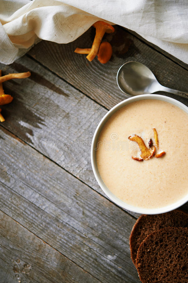 Mushroom cream soup. Plate of cream soup with chanterelle on rustic wooden table. top view stock photography