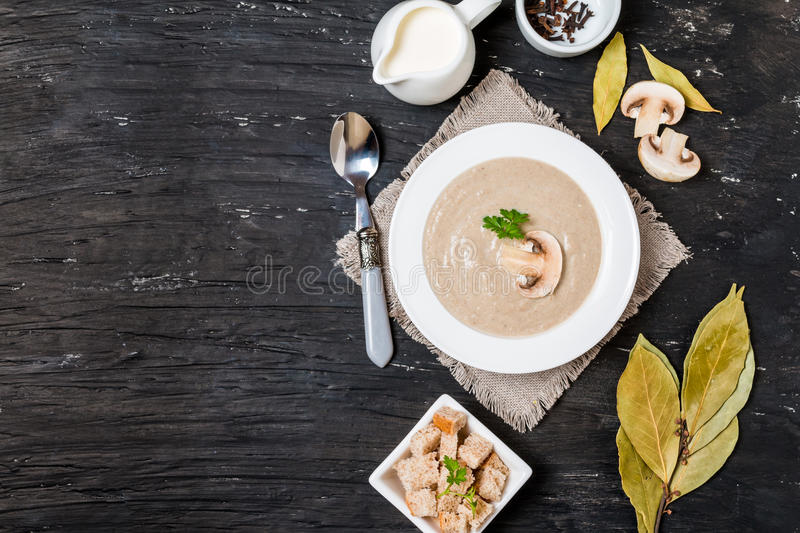 Mushroom cream soup. In a white bowl with seasoning on black background, top view royalty free stock photos