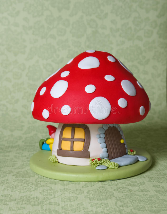 Mushroom Fantasy Cake. A children's birthday cake decorated as a cute fairy mushroom home with window and a door, and a little gnome taking a nap stock images
