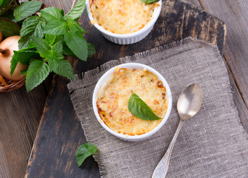 Mushroom and potato gratin. In white ceramic bowls, on wooden rustic background royalty free stock photo