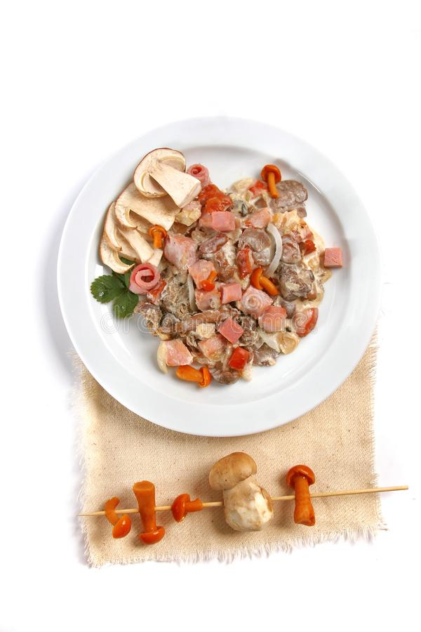 Mushroom salad with white mushrooms, honey agaric, bacon, served with parmesan cheese on white plate. close up stock photos