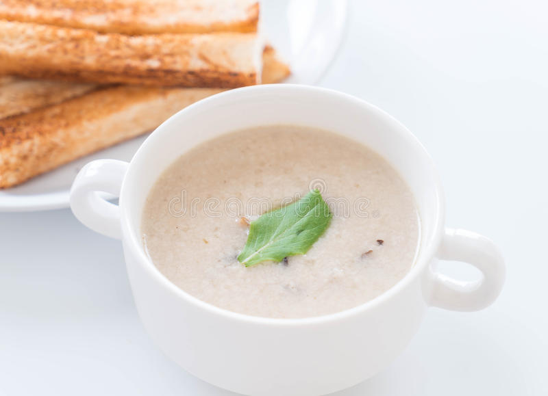 Mushroom soup and bread in white ceramic cup. On the table royalty free stock photography
