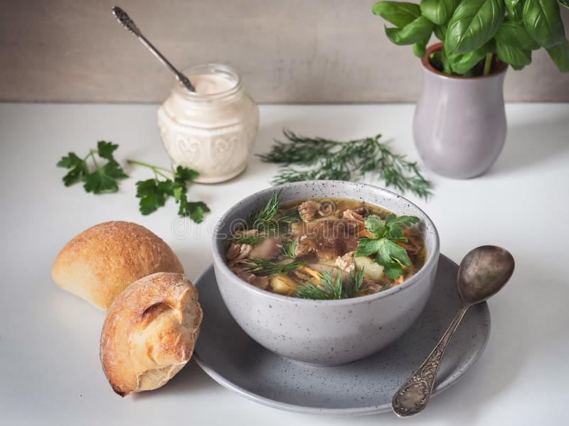 Mushroom soup in a deep gray ceramic plate. Bread rolls and fresh basil in a clay pot on a white table stock images