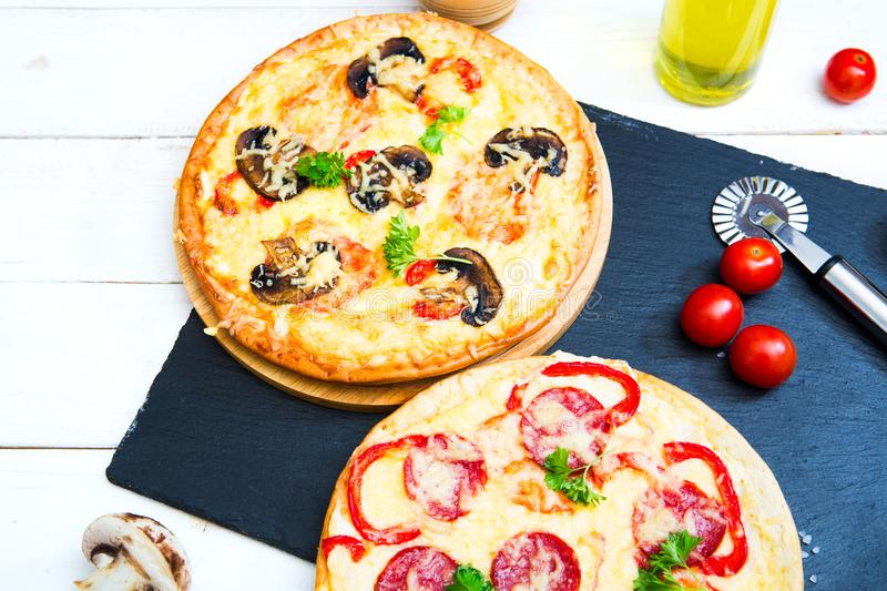 Mushroom and vegetable pizza and salami pizza at the back.  royalty free stock photography