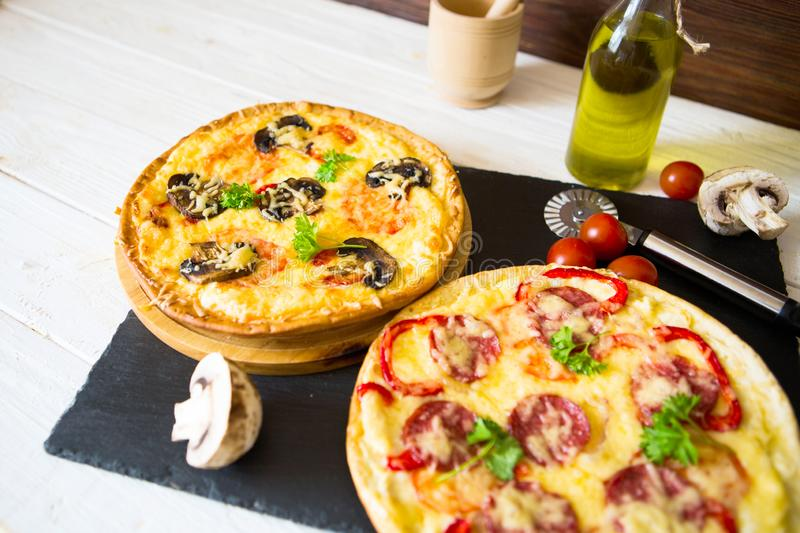 Mushroom and vegetable pizza and salami pizza at back. Mushroom and vegetable pizza and salami pizza at the back royalty free stock photos