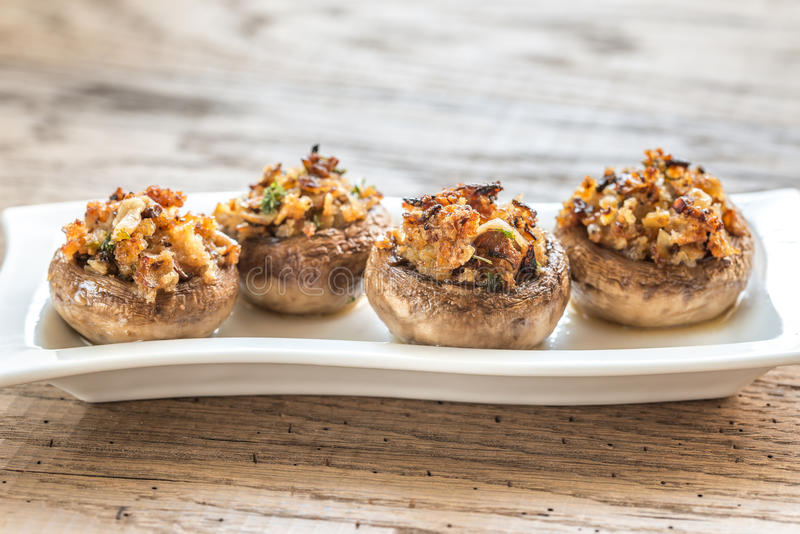 Mushrooms' caps stuffed with cheese, onion and butter stock photos