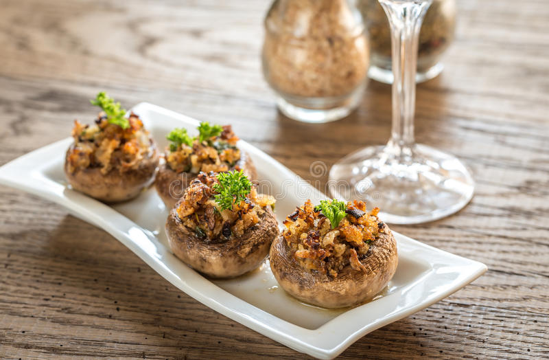 Mushrooms' caps stuffed with cheese, onion and butter royalty free stock image