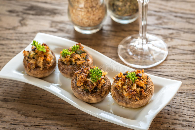 Mushrooms' caps stuffed with cheese, onion and butter stock image