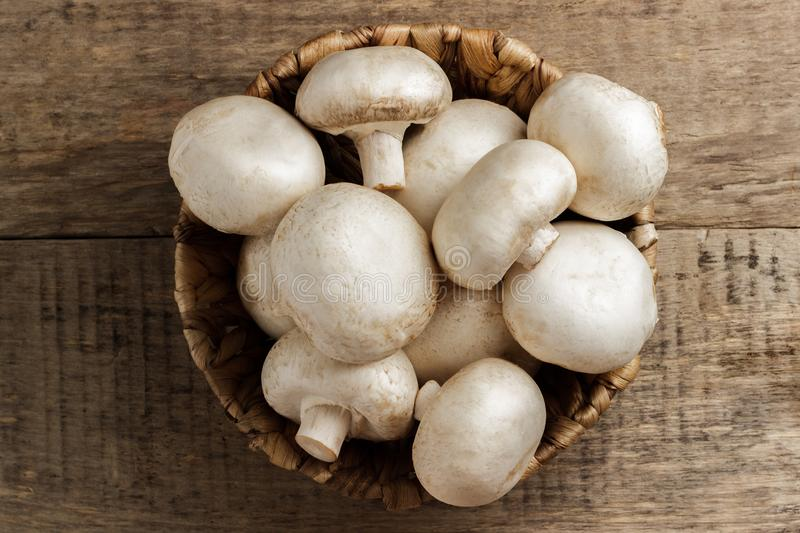 Mushrooms champignons in a wicker basket on a wooden background royalty free stock image