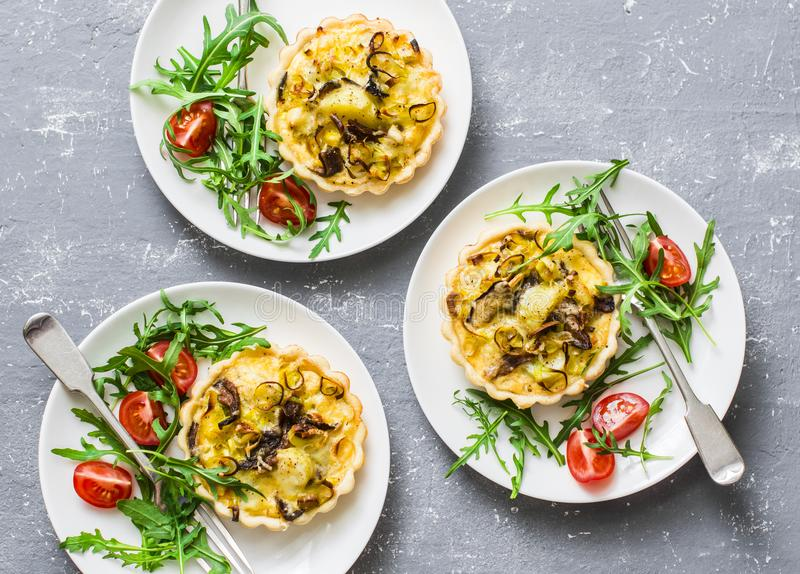 Mushrooms, cheddar mini pies on grey background, top view. Delicious appetizer, tapas, snack. Top view stock photography