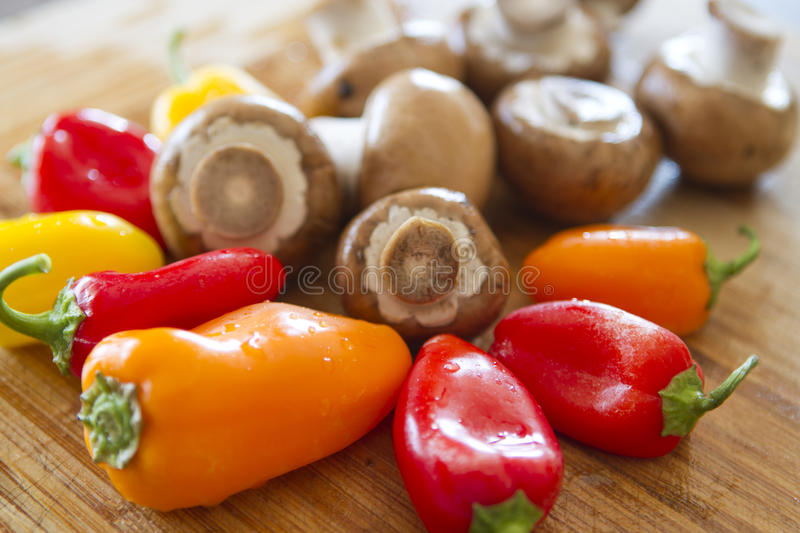 Mushrooms and colorful peppers waiting to be cut.