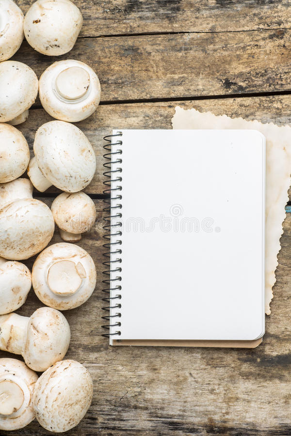 Mushrooms with cooking book or recipe sheet on wood background. Mushrooms with blank cooking book or recipe sheet on wood background royalty free stock photos