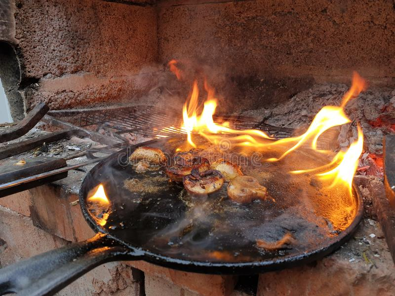 mushrooms in a frying pan on fire royalty free stock photo