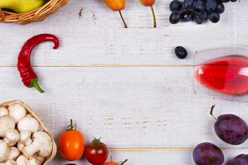 Mushrooms, grape, plums, onion, tomatoes, chilli peppers, glass of red wine, apples and pears in basket. View from above; top stud stock photos