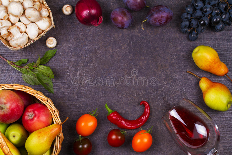 Mushrooms, grape, plums, onion, tomatoes, chilli peppers, glass of red wine, apples and pears in basket. View from above stock photography