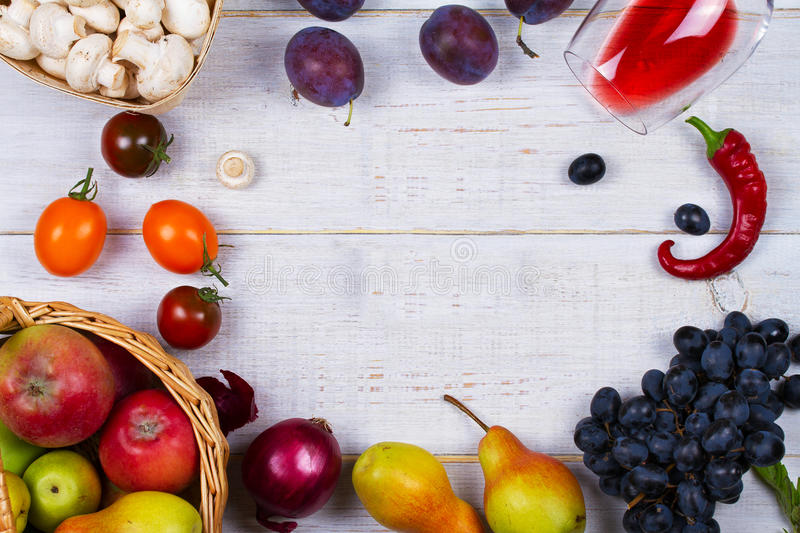 Mushrooms, grape, plums, onion, tomatoes, chilli peppers, glass of red wine, apples and pears in basket. View from above. Top studio shot stock photography